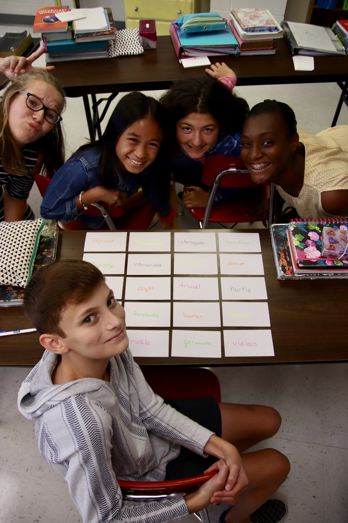 Four seventh graders pose for a picture during a vocabulary review lesson