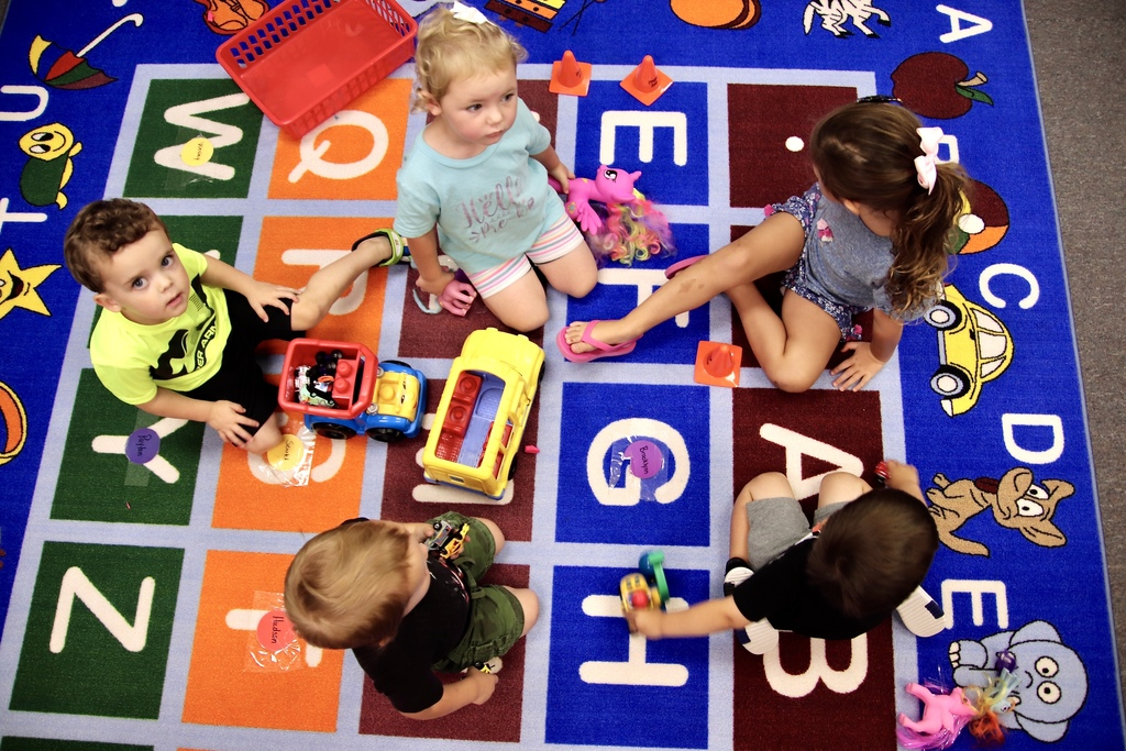 preschool students playing with toys in classroom - view from above