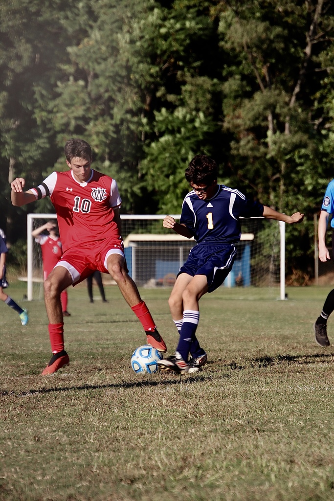 Varsity boys soccer player competing for the ball with a player from another team